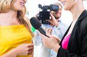 stock photo of tv sets  - Reporter and cameraman film shoot actress interview on film set for TV or  Television - JPG