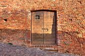 Red brick exterior wall of old house with wooden door on cobbled street in small italian town.