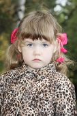 foto of overcoats  - Serious little girl with pink bows in overcoat looks at camera in forest - JPG