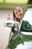picture of car key  - Happy woman sticking her head out of a car - JPG
