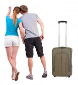 young couple traveling with suitcas and pointing at wal Back view. Rear view people collection.  bac
