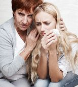 Mother soothes crying daughter. Mature woman calm young sad woman