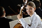 stock photo of cello  - Young beautiful woman playing cello in orchestra - JPG