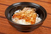 Japanese cuisine, eel with rice at black plate