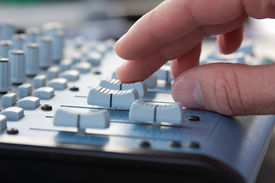 picture of recording studio  - Knobs of a sound mixer with a hand  - JPG