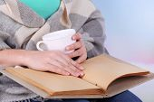 Woman reading book and  drink coffee or tea, close-up