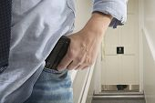 stock photo of bodyguard  - Bodyguard with gun protects client against an s water closet door background - JPG