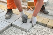 stock photo of brick block  - Construction site worker installing concrete brick pavement using hammer - JPG