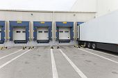 pic of semi trailer  - White semi truck trailer at warehouse loading dock - JPG