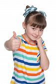 pic of shy girl  - A shy little girl holds her thumbs up against the white background - JPG