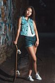 pic of skate board  - Beautiful Asian teen girl with skate board. Outdoors, urban lifestyle. ** Note: Soft Focus at 100%, best at smaller sizes - JPG