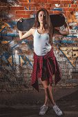 stock photo of skate board  - Beautiful Asian teen girl with skate board on shoulders. Outdoors, urban lifestyle.