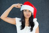 picture of fussy  - Closeup portrait of a cute Christmas woman with a red Santa Claus hat white dress finger on head confused thinking what to shop for the holiday season - JPG