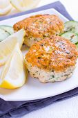 image of patty-cake  - Fried salmon patties served with fresh lemon and some cucumbers - JPG