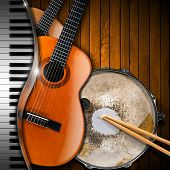 stock photo of bluegrass  - Two acoustic guitars piano keyboard and metallic old snare drum against a rustic wood background - JPG