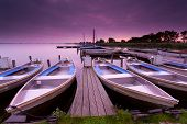 stock photo of pier a lake  - boats by pier on lake haven during sunrise Leekstermeer Netherlands - JPG