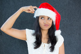 stock photo of fussy  - Closeup portrait of a cute Christmas woman with a red Santa Claus hat white dress finger on head confused thinking what to shop for the holiday season - JPG