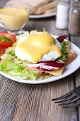 picture of benediction  - Toast with egg Benedict and tomato on plate on wooden table - JPG
