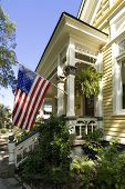 picture of waving american flag  - Beautiful restored old turn of the century home proudly displaying an American Flag - JPG
