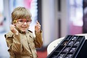 image of spectacles  - Cute little kid boy at optician store during choosing his new glasses.