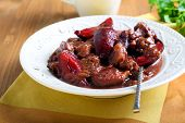 picture of stew  - Pork stew with plums served in a plate - JPG
