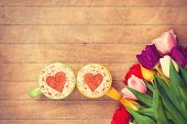 foto of two hearts  - Two cups of Cappuccino with heart shape symbol and tulips on wooden background - JPG