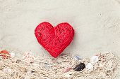 stock photo of beach shell art  - Heart shape toy and net with shells on sand background - JPG