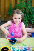 stock photo of big-girls  - A family picture of children having fun painting and decorating Easter eggs outside. A portrait of a happy little girl in a pink dress sitting at a crafts table posing with a big smile holding her dyed blue egg during the spring season  ** Note: Visible  - JPG