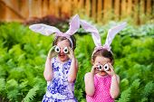 stock photo of ear  - A funny portrait of two girls having fun on Easter wearing bunny ears and holding up silly eyes made from eggs outside in a garden during the spring season - JPG