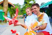 picture of child feeding  - excited family feeding colorful pigeons on animal farm - JPG