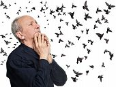 stock photo of 55-60 years old  - Elderly man looking up on sky with flying birds - JPG