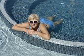 stock photo of prone  - High angle view of aged woman that is lying prone in bright blue water of swimming pool - JPG
