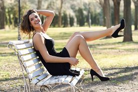 pic of sitting a bench  - Portrait of funny woman model of fashion with very long legs sitting on a bench in an urban park wearing black dress and high heels - JPG