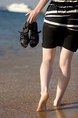 pic of barefoot  - Young woman walking barefoot through the surf on the seashore holding in hands blue leather sandals close up back view white yacht on the background - JPG