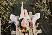 picture of wet  - girl in a flower wreath on his head sitting on the bridge and wets feet in the river - JPG