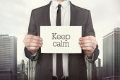 foto of calming  - Keep calm on paper what businessman is holding on cityscape background - JPG