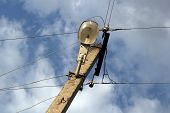 stock photo of corbel  - Old concrete pillar with lamp wires and insulators over sky photo - JPG