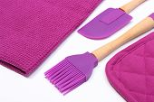 stock photo of purple white  - Closeup of purple silicone kitchen accessories spatula and brush with purple cloth composition of colors purple - JPG