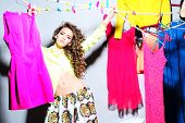 foto of jeans skirt  - Sensual pretty young girl with curly hair in skirt and blouse standing amid colorful clothes pink orange red blue colors on grey wall background horizontal picture - JPG