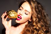 picture of bread rolls  - Attractive pretty young girl with curly hair and bright pink lips holding golden bread roll near face standing with closed eyes and open mouth on dark grey background horizontal picture - JPG