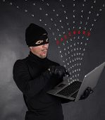 stock photo of stealing  - Hacker stealing data from a laptop on black background - JPG