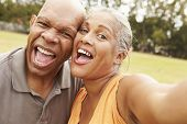picture of two women taking cell phone  - Senior Couple Taking Selfie In Park - JPG