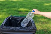 image of throw up  - Close up hand throwing empty plastic bottle into the trash - JPG