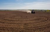 picture of plowing  - Blue Tractor plowing a field before planting seeds - JPG