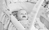 pic of teething baby  - Happy baby lying in the cradle and looking at toys  - JPG