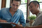 foto of mans-best-friend  - Two Men Using Tablet, Asian Mix Race Friends Guys Sitting at Cafe Natural Light ** Note: Visible grain at 100%, best at smaller sizes - JPG