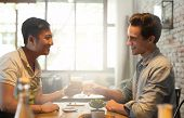 stock photo of mans-best-friend  - Two Men Cheers Toast Drink, Asian Mix Race Friends Guys Happy Smile Sitting at Cafe Natural Light ** Note: Visible grain at 100%, best at smaller sizes - JPG