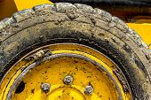 stock photo of mud  - Extreme close up of tire bulldozer yellow and covered with mud - JPG
