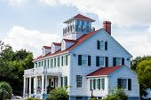 image of gabled dormer window  - Cliassic white home with red roof dormers and widows walk - JPG