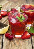 foto of cold drink  - Cold strawberry and cherries drink with fresh strawberriescherries and lemon on wooden background - JPG